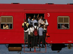 People hang onto a crowded local passenger train as they travel to Colombo March 11
